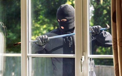 Person mit Skimaske bricht durch Fenster ein - IT-Security
